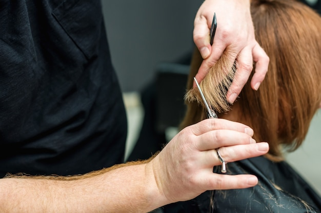 Closeup of hairdresser's hands are cutting client's hair in salon.