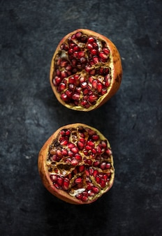 Closeup of half fresh pomegranate on black background