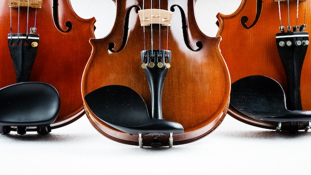 Closeup half front side of three violins put on background, show detail and part of violin