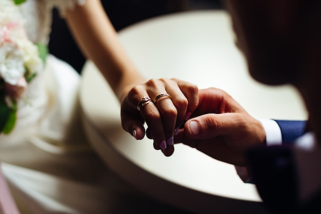 Closeup of the hand of the bride with beautiful rings that the groom holds
