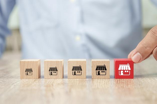 근접 촬영 손 나무 큐브 블록 프랜차이즈 비즈니스 스토어 아이콘을 선택
