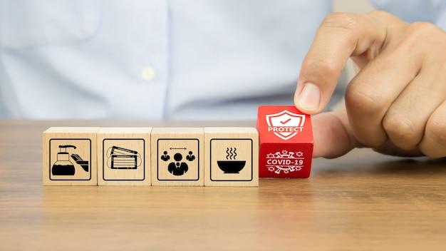 Рука крупным планом, выбирая значок защиты от covid на деревянных игрушечных блоках