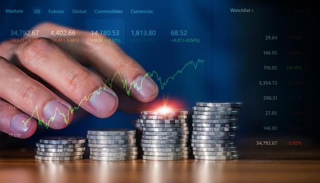 Крупным планом рука подсчета монет стек на столе в концепции бизнес-инвестиционной торговой фондовой бирже, торговый онлайн-трейдер с цифровой диаграммой