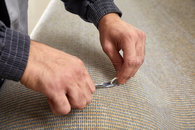 Closeup of hand cutting off string on a carpet with scissors. carpet cleaning service