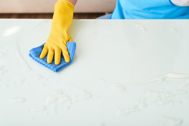 Closeup of hand in glove cleaning table with foam detergent