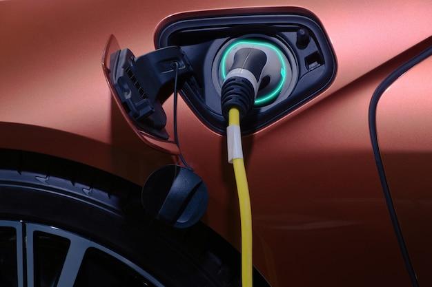 充電式バッテリー用の茶色の電気自動車のソケット充電に接続されたクローズアップハンドグリッププラグ