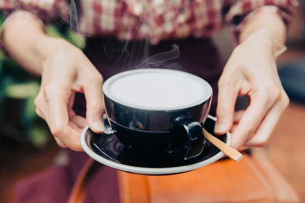 Closeup hand hold serve hot milk white creamy healthy drink for everyday