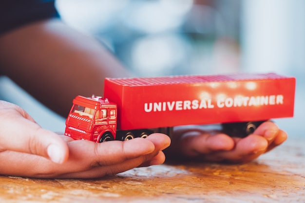 クローズアップの手は、ロジスティクスとビジネスコンセプトに使用する赤いトラックユニバーサルコンテナを保持します