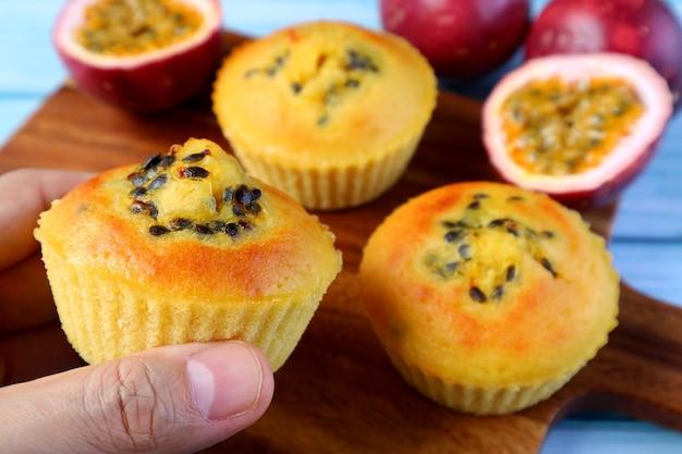 バックグラウンドでぼやけたカップケーキと新鮮な果物とパッションフルーツのマフィンを持っているクローズアップの手