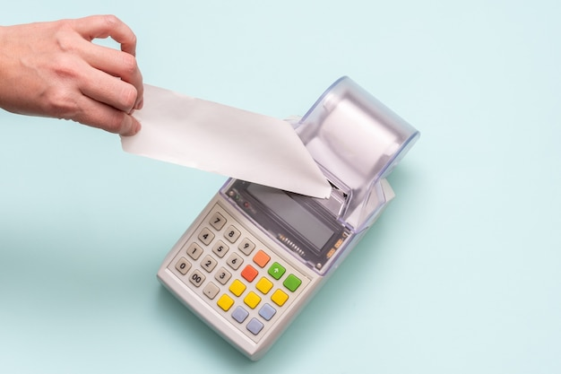 Closeup of a hand holding a blank white check on a cash register black friday concept