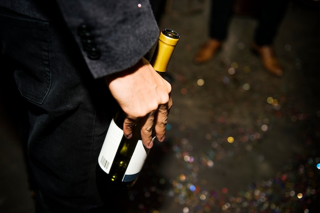 Closeup of hand holding champagne bottle