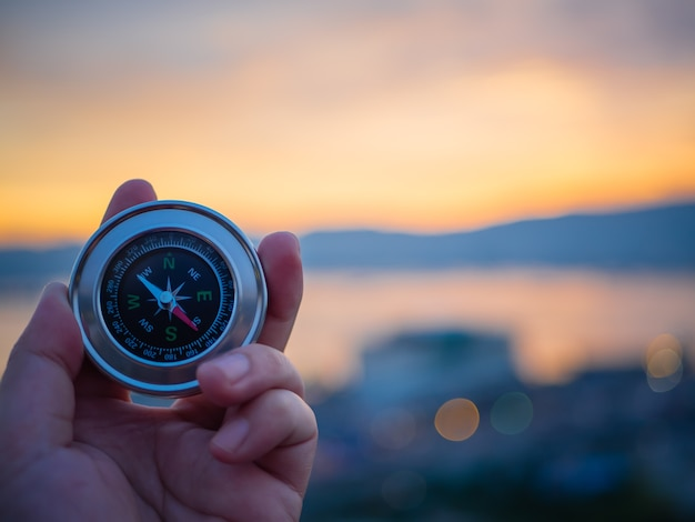 Closeup hand holding compass with  mountain and sunset sky background