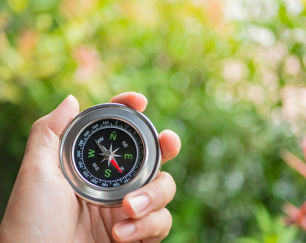 Closeup hand holding compass with  tree leaves bokeh background.