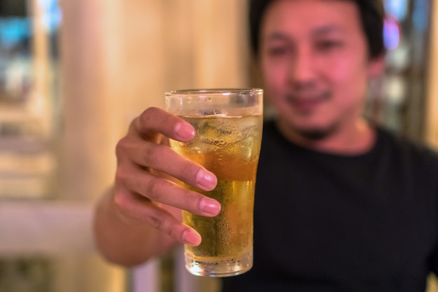 Closeup hand holding glass of beer from asian young man in happiness action in pub and res