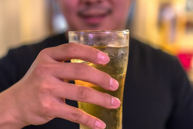 Closeup hand holding glass of beer from asian young man in happiness action in pub