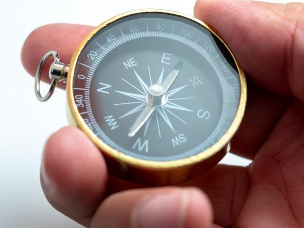 Closeup hand holding golden compass