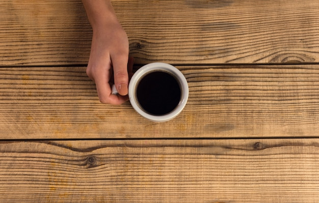 Closeup hand holding a mug of coffee on a wooden table.