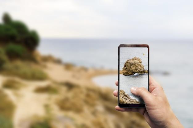 Primo piano di una mano che tiene un telefono mentre scatta una foto di una spiaggia