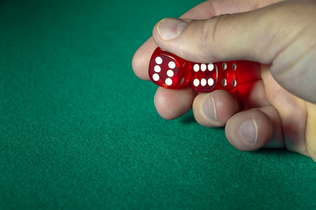 Closeup of hand holding red dice with a winning combination on green cloth in a casino.