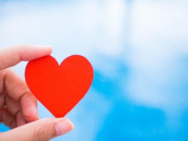 Макрофотография рука, красная форма сердца бумаги на синем фоне