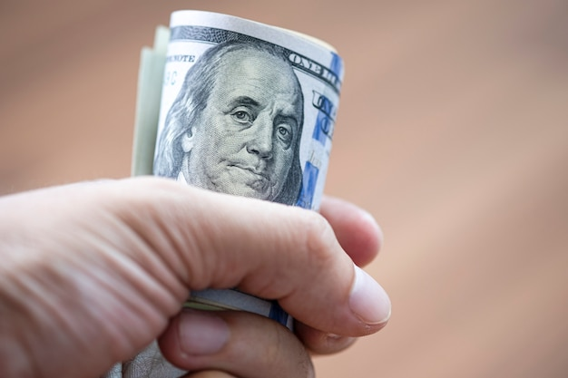 Closeup of hand holding roll of us dollar banknote for paying someone