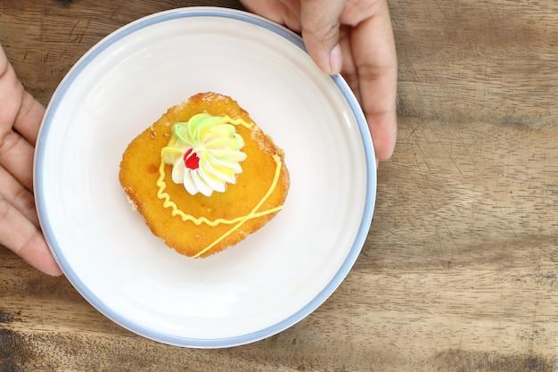 근접 촬영 손을 잡고 태국 오렌지 잼 케이크 디저트의 조각이 하얀 접시.