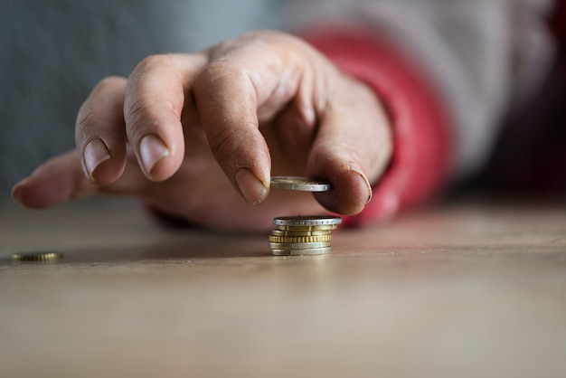 Closeup of hand of a homeless man with dirty nails making stack of euro coins in a conceptual image.