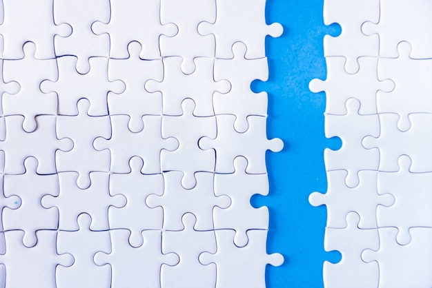 Closeup hand of man connecting jigsaw puzzle with sunlight effect