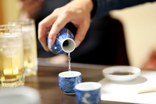 Closeup hand of man pouring japanese sake into sipping ceramic bowl on the wooden table. japanese drink style. warm tone.