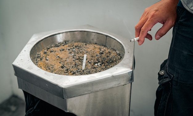 Closeup hand of a man with cigarette. people smoking in smoking zone area of the mall and left cigarette in ashtray. quit smoke or smoking cessation and lung cancer.