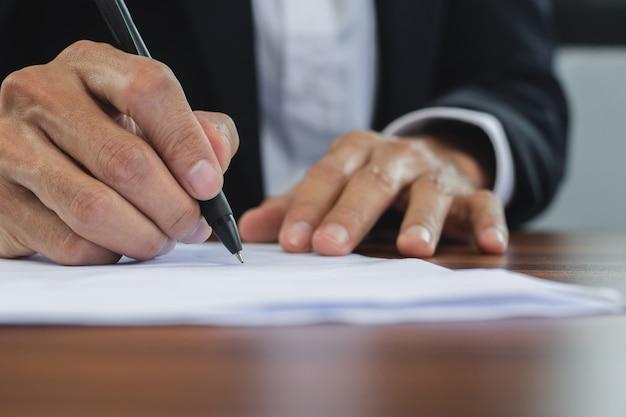Подпись менеджера руки крупным планом на документе, знак контакта бизнес в концепции офиса