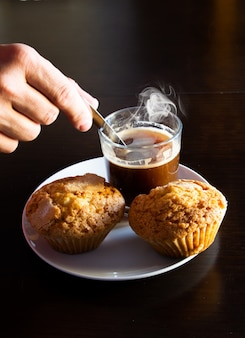 Closeup of hand mixing coffee with a spoon next to fresh muffins