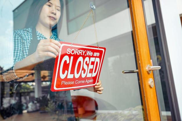 고객을 환영하기 위해 상점 안경에 닫기 기호를 설정하는 아시아 젊은 여성의 근접 촬영 손