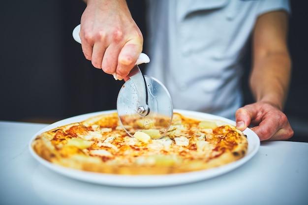 부엌에서 흰색 균일한 절단 피자를 입은 요리사 제빵사의 손을 클로즈업.