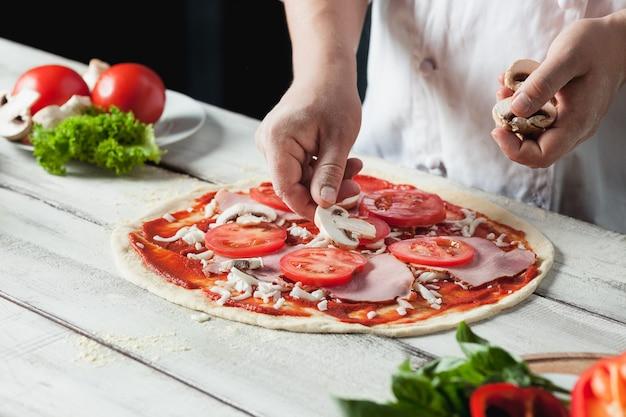 Крупным планом рука шеф-повара пекаря в белой форме, делая пиццу на кухне