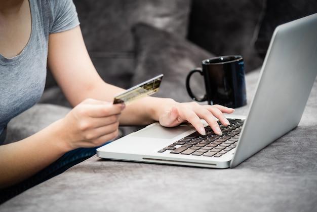Sme 신용 카드를 들고 키보드 노트북 컴퓨터를 사용하여 온라인으로 제품 지불 쇼핑을 하고, 돈을 쓰고, 전자 상거래, 인터넷 뱅킹, 집 개념에서 원격으로 일하는 여성의 클로즈업