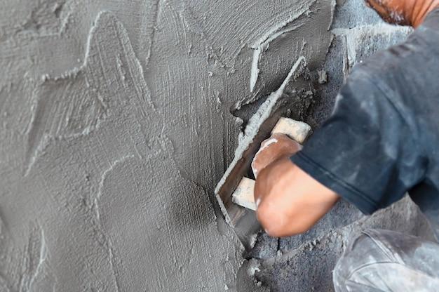 Крупным планом рука работника штукатурки цемента на стене на строительной площадке