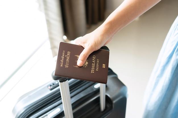 ホテルの部屋でパスポートを保持している若いアジア人旅行者のクローズアップの手。休日のコンセプト