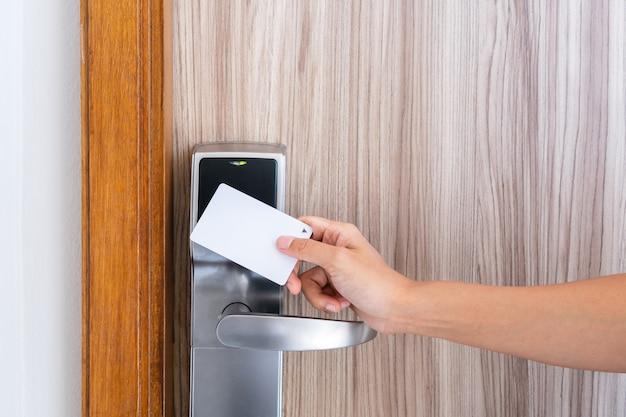 키 카드를 사용하여 호텔 도어의 전자 센서를 잠금 해제하는 젊은 아시아 여성의 근접 촬영 손