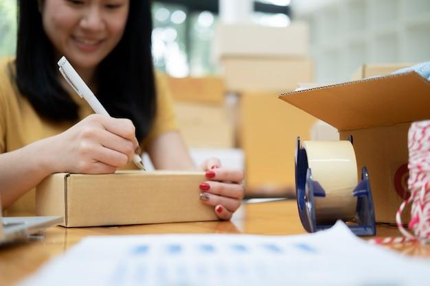 Крупным планом рука молодой женщины, пишущей адрес на посылочной коробке для заказа доставки клиенту, отгрузка и логистика, онлайн-торговец и продавец, владелец бизнеса или мсп, интернет-магазины.