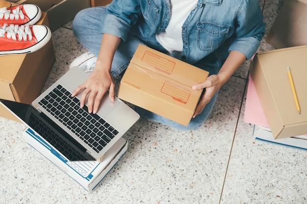 Крупным планом рука молодой женщины, написание адреса на посылочной коробке для заказа доставки клиенту, отгрузка и логистика, онлайн-торговец и продавец, владелец бизнеса или sme, интернет-магазины.