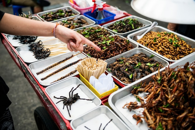 Closeup of hand ordering cooked insects in thailand street food stall