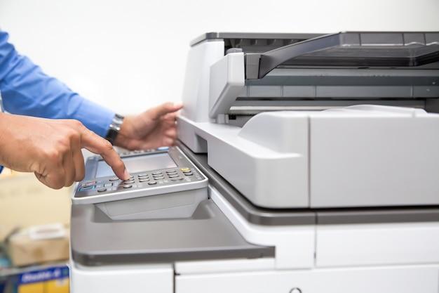 Closeup hand press button to using the photocopier.