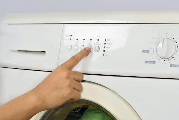 Closeup of hand push the button on washing machine