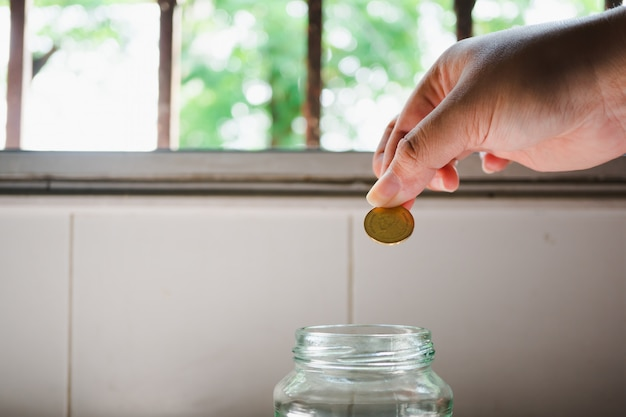 Closeup hand put coin into bottle using as money saving and business concept