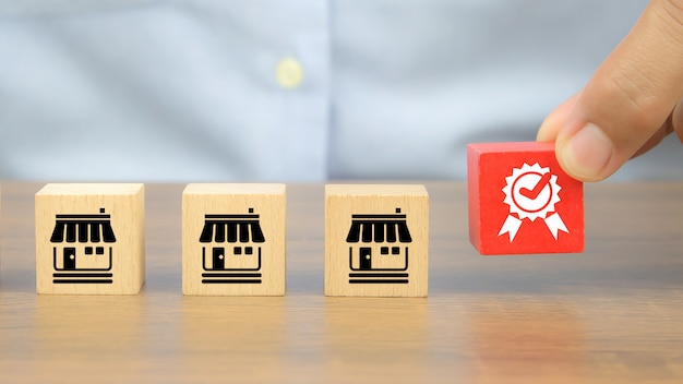 Closeup hand and quality symbol on wooden cubes with franchise business store icons