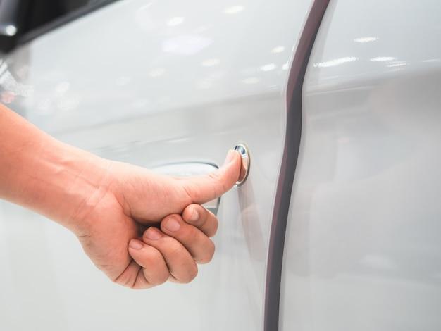 Крупным планом рука сканирование двери автомобиля белого цвета и размытие концепции автосалона