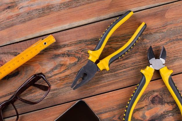 Ручные инструменты крупным планом включают плоскогубцы линейки на коричневом деревянном столе