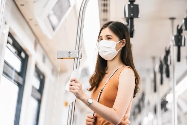 외과용 마스크를 쓴 젊은 아시아 여성 승객의 젖은 닦음으로 손을 만지는 클로즈업