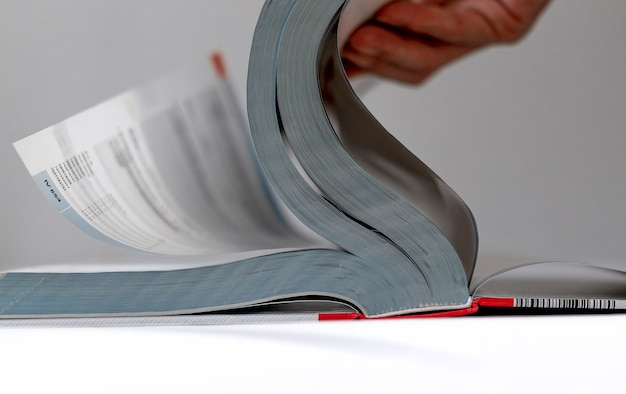Крупным планом рука переворачивает страницы чтения и изучения технических книг